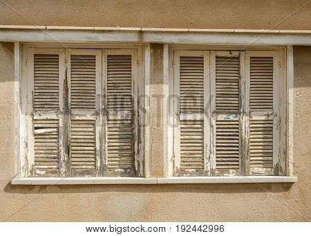 Old windows with closed worn flaking shutters.