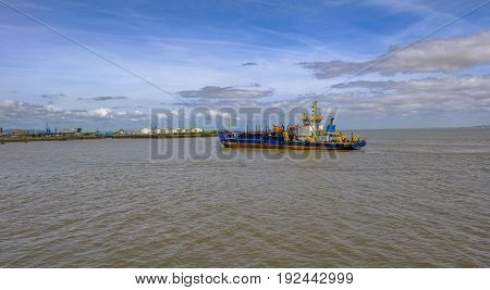 Ship retunring to port at Cardiff Wales. Early summer shot of a dredger sailing.