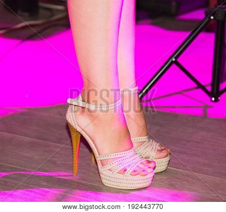 Feet of a girl on stilettos on stage.