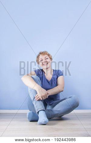 Average Blond Woman Sitting On The Floor Cross-legged