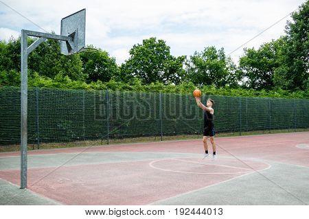 Teenage boy shooting a basketball on a court