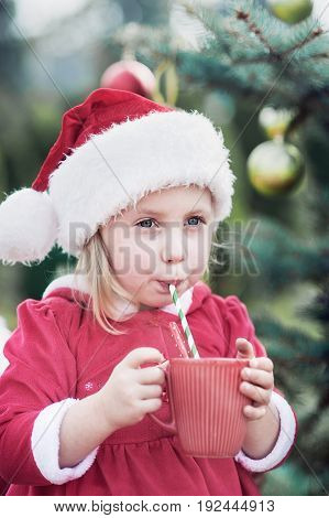 Little girl waiting for a Christmas in the wood. Christmas in juli. Cute child holding big cup with hot cocoa and chocolate drink and marshmallows.