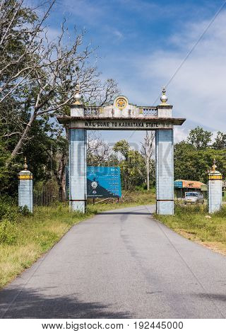 Karnataka India - October 26 2013: Light blue welcome gate on the state line with Tamil Nadu at Bandipur Tiger Reserve and National Forest. Blue sky jungle vegetation narrow road car and monkey.