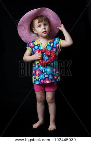 Little girl actress in a hat, holds a heart in her hands and looks surprised
