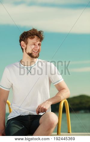 Happy fashion young man guy relaxing enjoying summer sunny day outdoor. Vacation holiday.