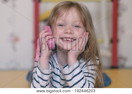 Little girl playing with toy. She pretends that she speaks on toy phone and smiles