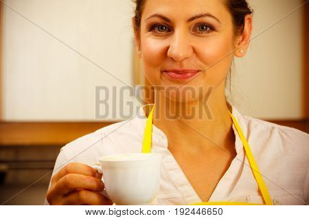 Mature woman in apron with cup of coffee in kitchen. Housewife female with hot beverage.