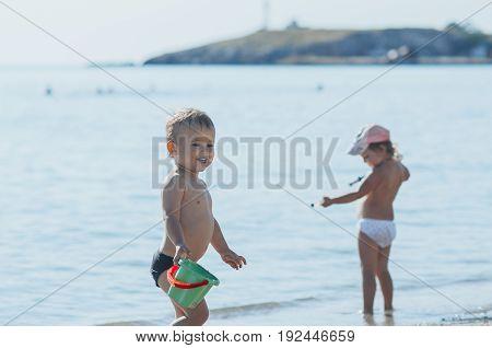 Little Boy With A Bucket Building Sandcastles On The Beach