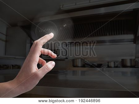Digital composite of Hand touching  air of chefs kitchen