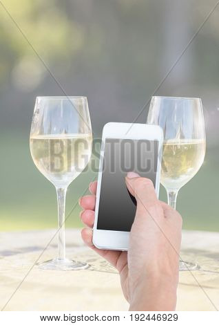 Digital composite of Hand holding phone with two glasses of champagne and sunny greenery