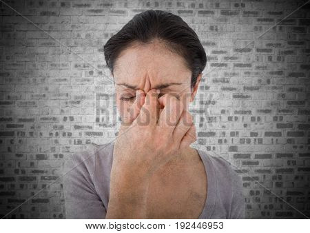 Digital composite of Woman stressed against white brick wall with grunge overlay