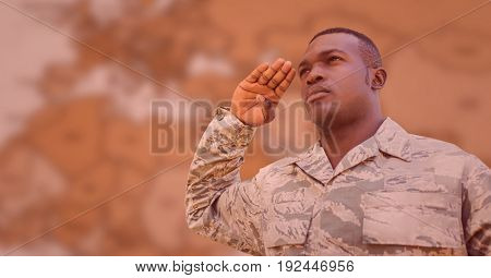 Digital composite of Soldier saluting against blurry brown map with red overlay