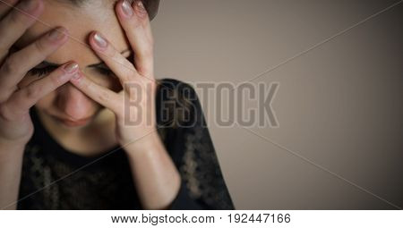 Digital composite of Woman hands over face against brown background