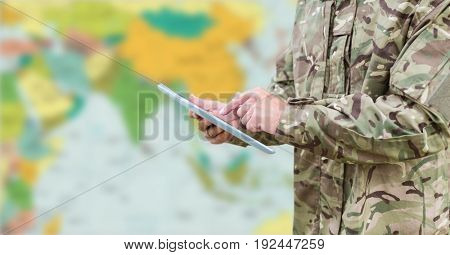 Digital composite of Soldier mid section with tablet against blurry map