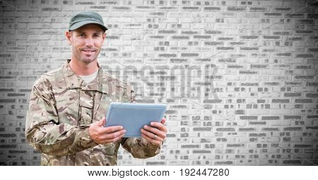 Digital composite of Soldier with tablet against white brick wall