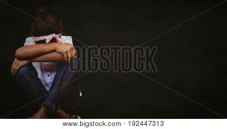 Digital composite of Girl with head between knees against black background with grunge overlay