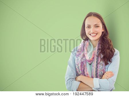 Digital composite of Casual businesswoman with arms crossed over green background
