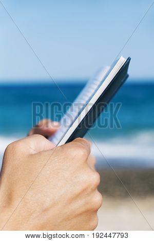 closeup of a young caucasian man reading a book on the beach