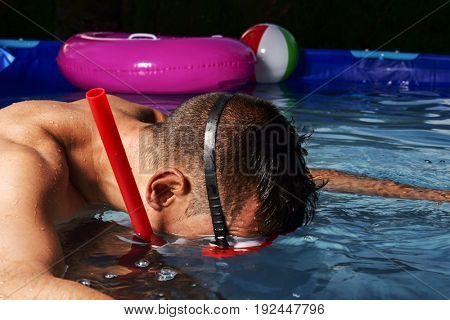 closeup of a young caucasian man wearing a diving mask and a snorkel diving in a portable swimming pool placed in the backyard