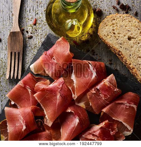 high-angle shot of some slices of spanish serrano ham on a slate tray, some slices of bread and a glass cruet with olive oil on a gray rustic wooden table