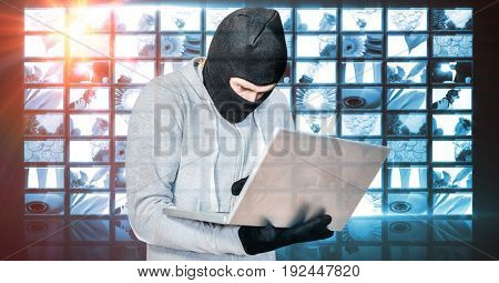 Digital composite of Hacker wearing monkey cap while using laptop