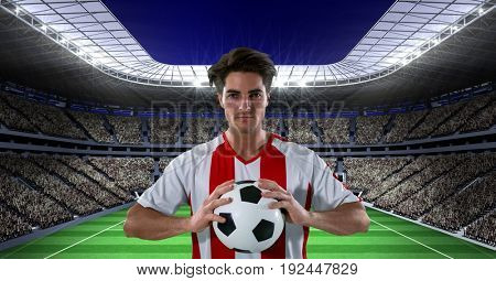 Digital composite of Confident soccer player holding ball at stadium