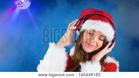 Digital composite of Smiling woman wearing Santa hat while listening music against blue background