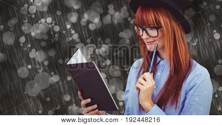 Digital composite of Young woman holding pen while reading book in rainy season