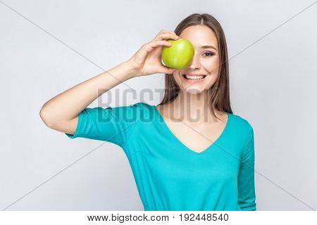 Young beautiful woman with freckles and green dress holding apple in front of her eyes and smiling . studio shot isolated on light gray background.