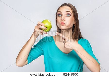 Young beautiful woman with freckles and green dress holding and eating apple and pointing and looking at camera with big eyes. studio shot isolated on light gray background.