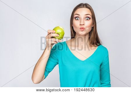 Young beautiful woman with freckles and green dress holding and eating apple and looking at camera with big surprised eyes. studio shot isolated on light gray background.