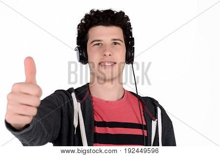 Portrait of young latin man listening music with black headphones and thumb up. Isolated white background.
