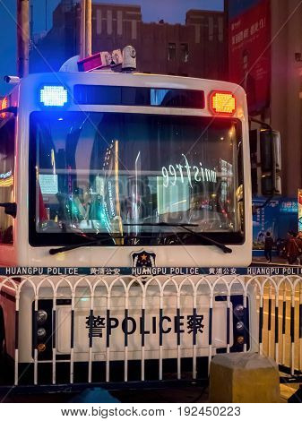 Shanghai, China - Nov 4, 2016: Night scene along Nanjing Road Pedestrian Street - A parked police van to help maintain public peace. Low-light street photography.