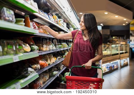 Smiling woman doing shopping in supermarket and deciding what to buy. Happy woman shopping in a grocery store and holding shopping basket. Mature latin woman buying vegetable in a grocery shop.