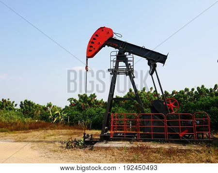 Oilfield Pump jack (rocking horse or pumpjack) over a wellhead on Sunny Day with clear sky.