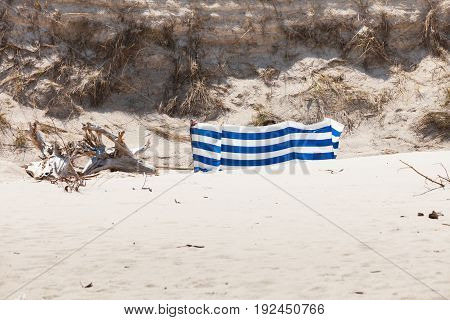 Blue And White Windbreak On Sandy Beach.