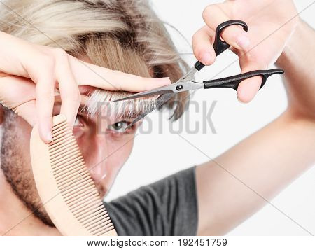 Style and fashion. Young trendy male hairstylist barber with new idea of look changing. Blonde guy with scissors and comb creating coiffure cutting his bangs.