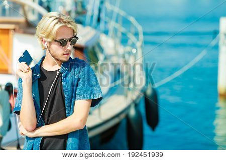Vacation relaxation passion concept. Young fashionable blonde in sunglasses man relaxing listening to music and enjoying beautiful sunny weather. Outdoor shot