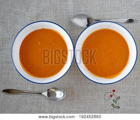 A pair of white bowls with creamy tomato soup