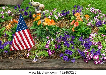 American flag in a vibrant flower garden on the fourth of July