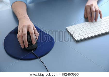 Female hands with computer mouse and keyboard on table