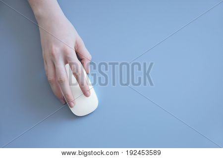 Female hand holding computer mouse on grey background