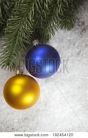 Multicolored balls and fir branch on snow