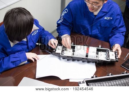 jinhua,china-Jan 23,2017:technicians discussing technique of product in manufacturing factory