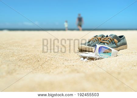 Close up of sunglasses, cell phone and shoes on the beach with blurred silhouttes of man and child on background