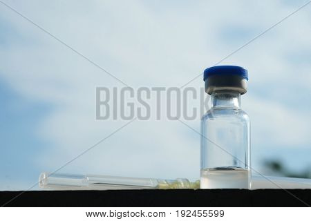 syringe and vial of vaccine place on the floor
