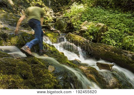 Man hiking over waterfall, motion blur from hiking.