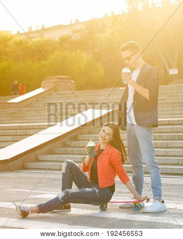 Teenagers on a date. A loving couple in a city park. A girl drinks fruit fresh after skating on a skateboard. Boyfriend is standing next to him and also drinking fruit fresh.