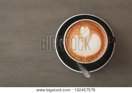 Top view of Latte hot coffee (or cappuccino) in a black cup with latte art on gray wooden table background.