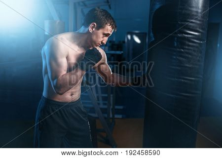 Man in black handwraps exercises with bag in gym